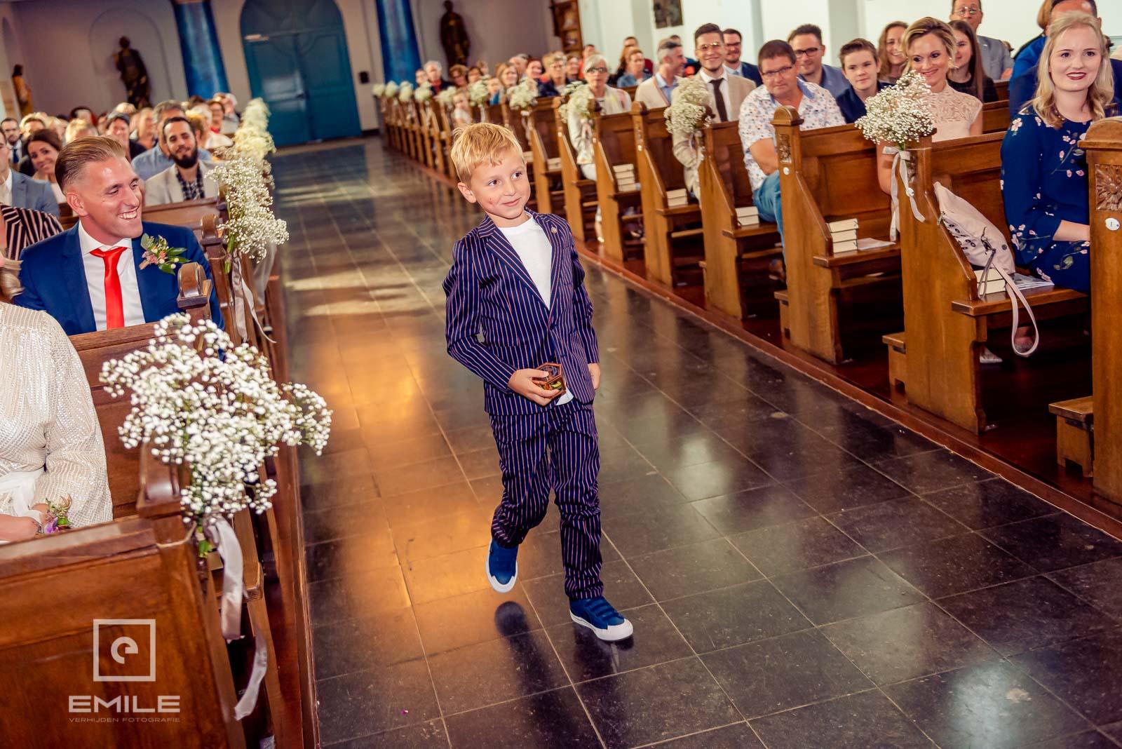 Bruidsjongen komt de ringen brengen in de kerk. Bruiloft Wylre Zuid-Limburg