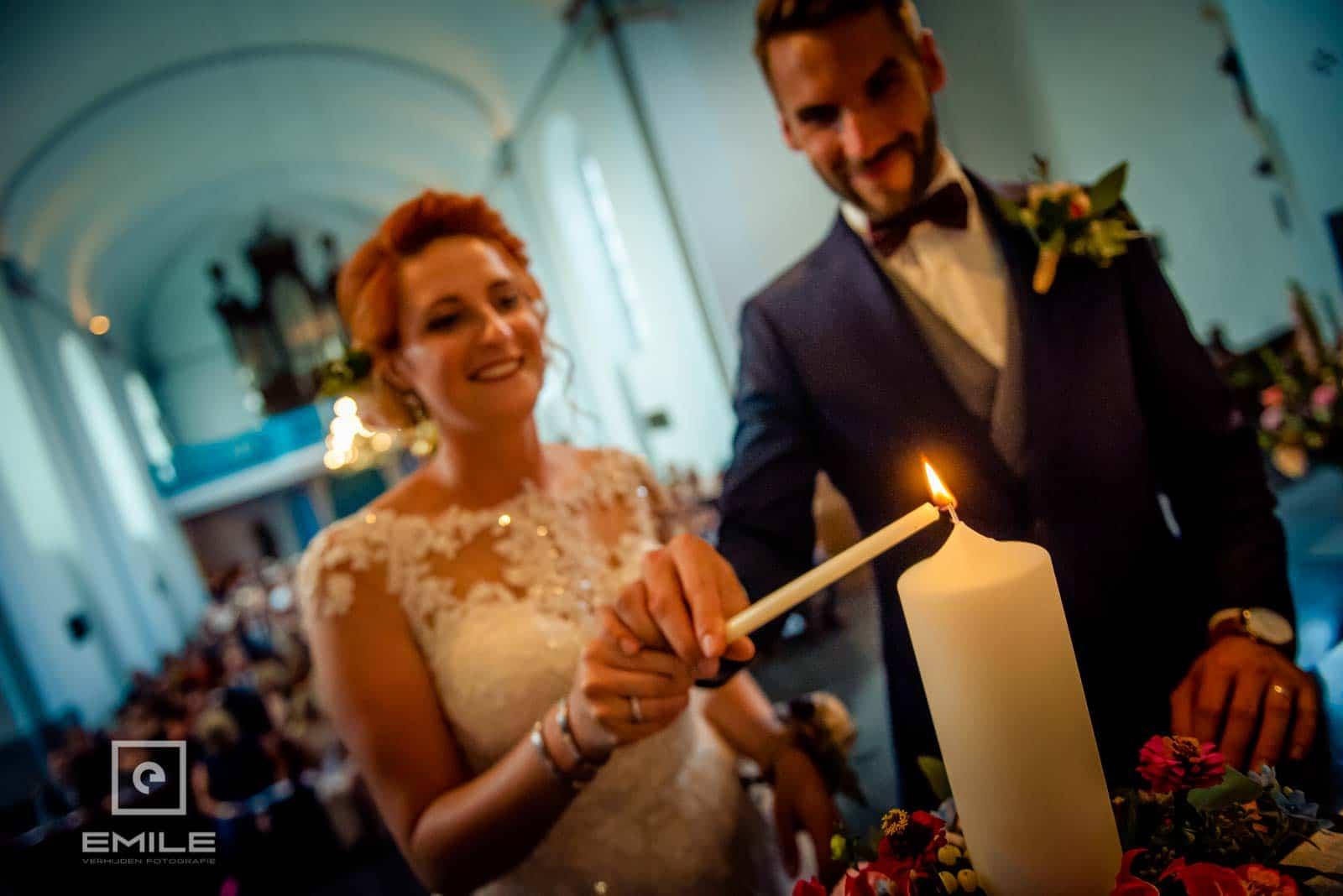 De huwelijkskaars wordt aangestoken door bruidspaar in de kerk