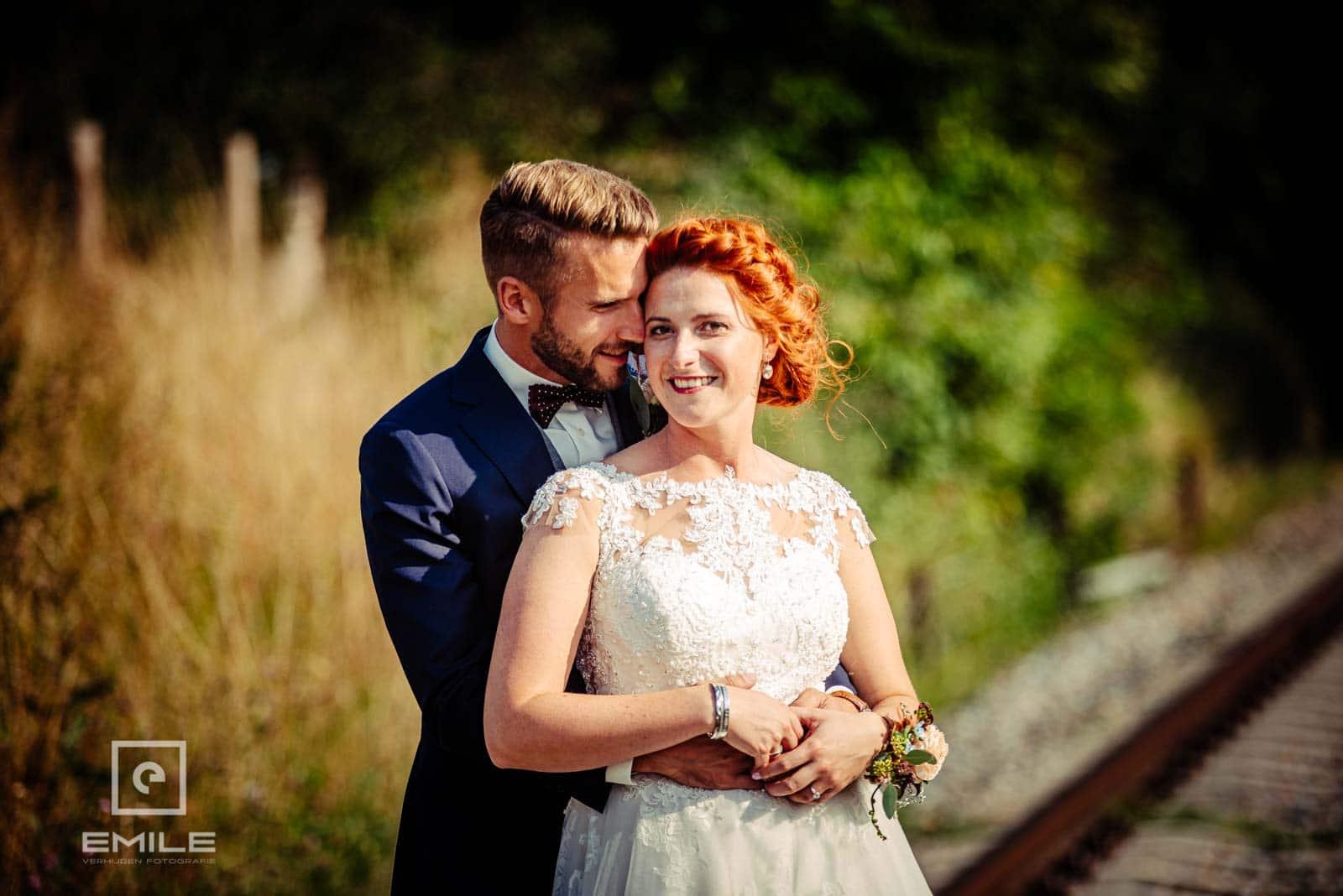 Bruidspaar samen op de foto bij het spoor van Wylre