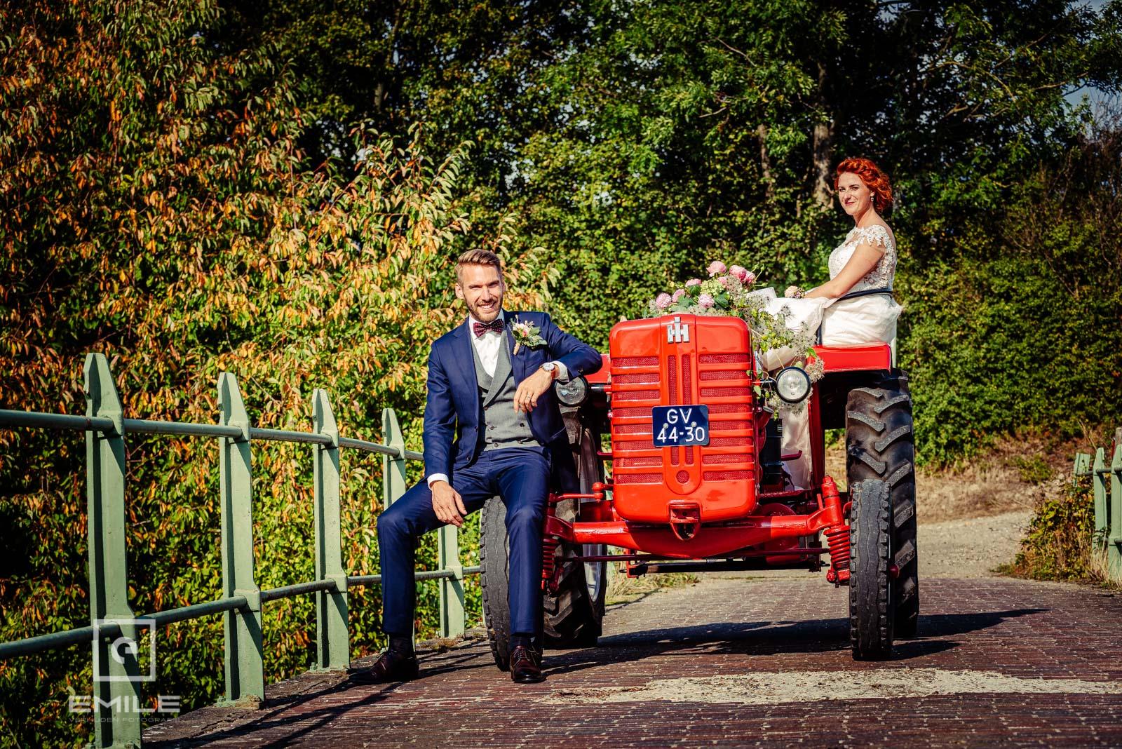 Stoere bruidegom zit op de band van de tractor in Wylre