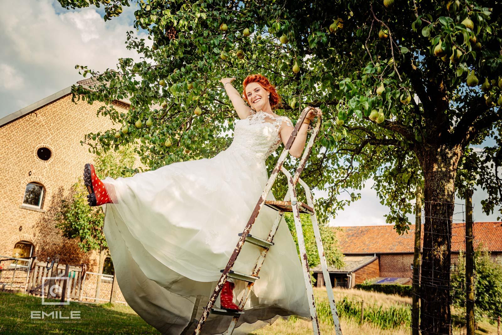 Happy bruid op de ladder. Bruiloft Limburg - Wylre