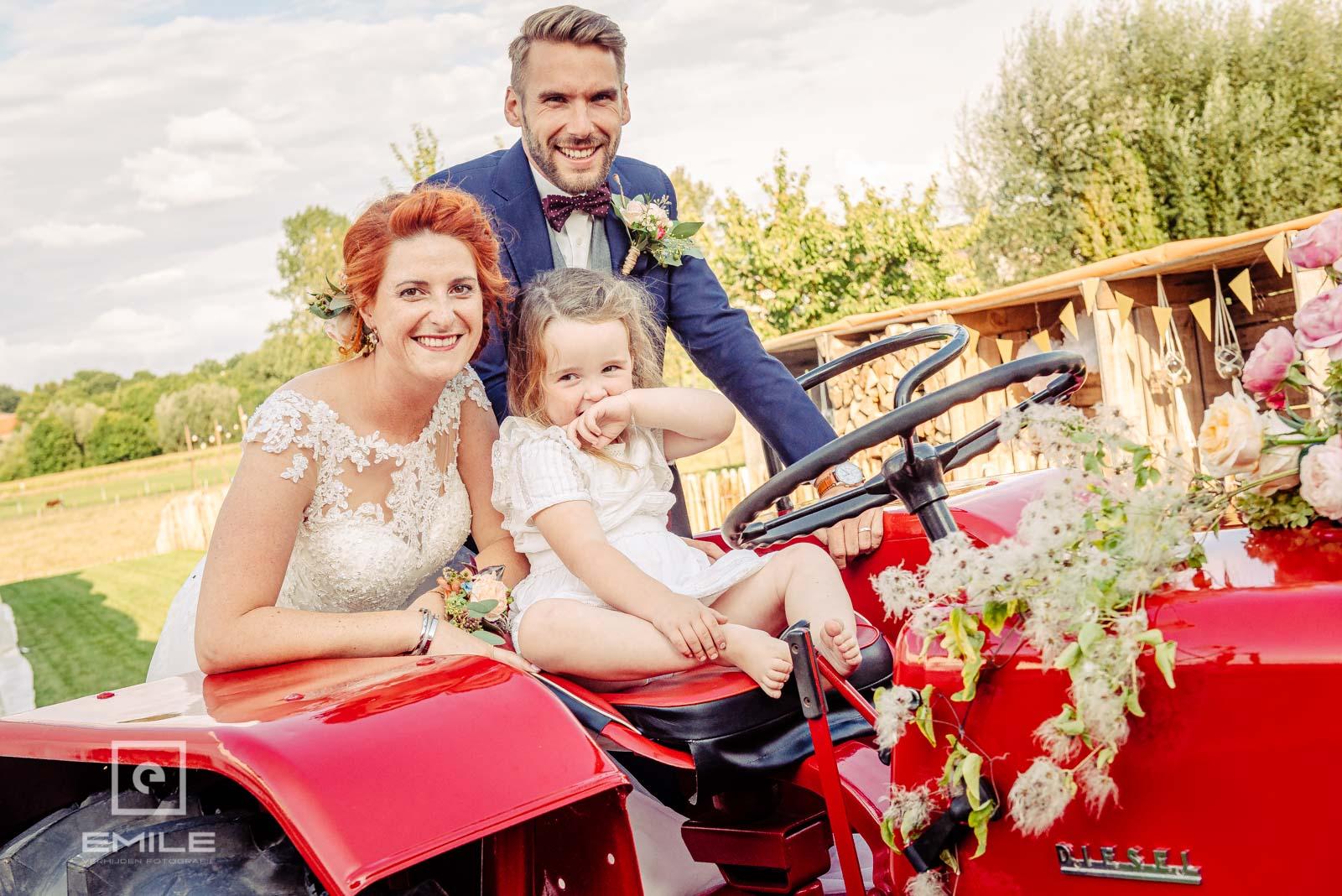 De kleine meid wil ook poseren op de tractor. Trouwen in Limburg