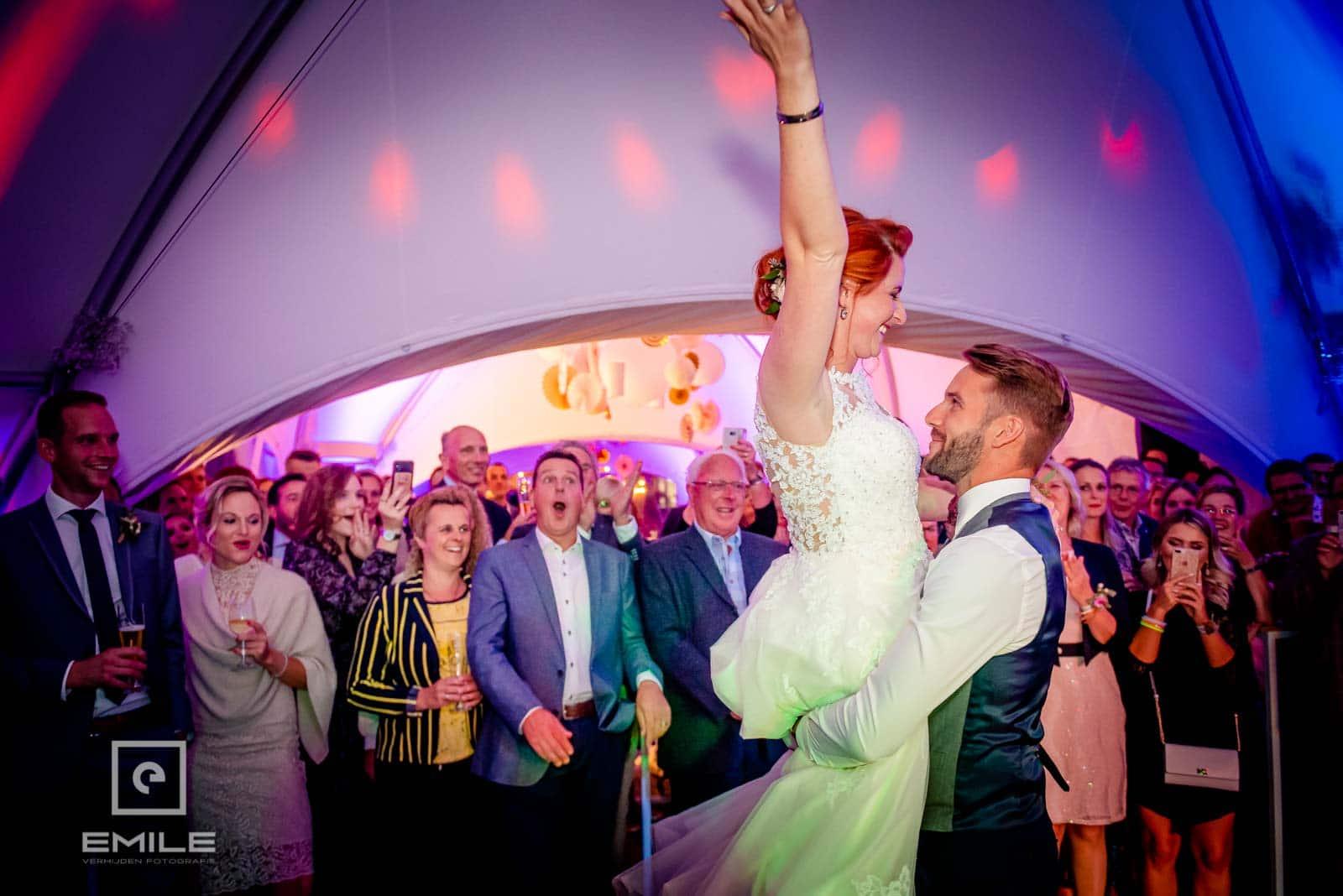 De bruid wordt in de lucht getild. Trouwen in Limburg