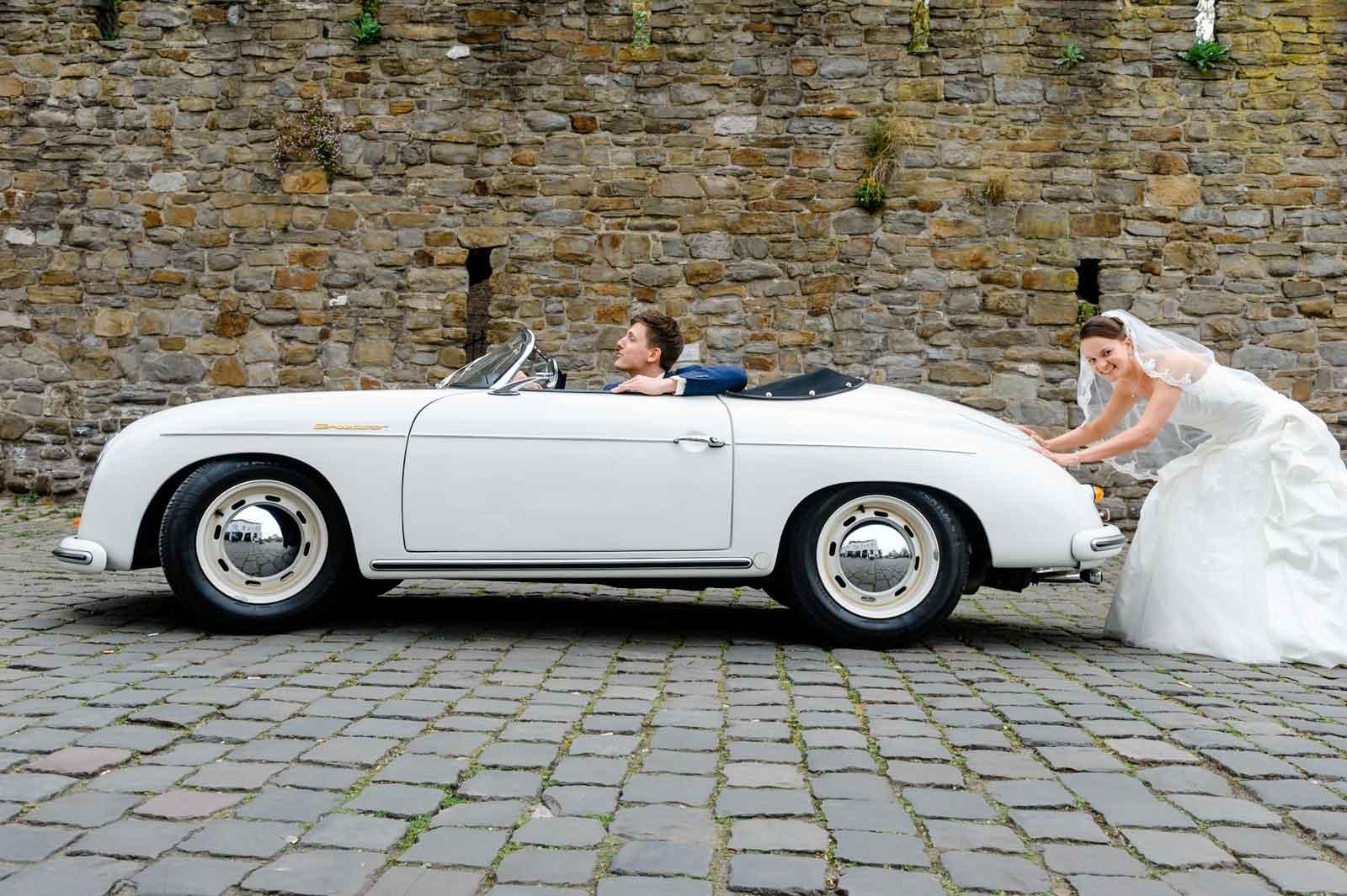 Bruid duwt old-timer trouwauto vooruit bij de helpoort Stadspark te Maastricht