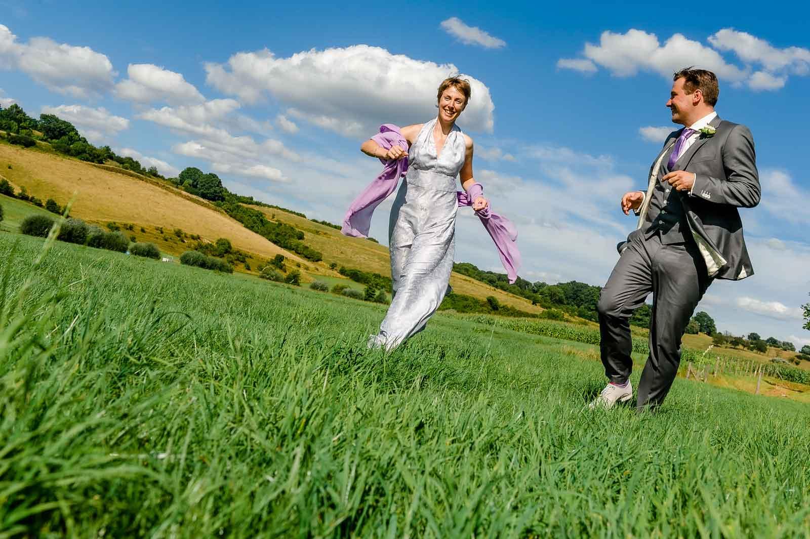 Bruid en bruidegom rennen door de wei bij Viva Lanterne Wittem