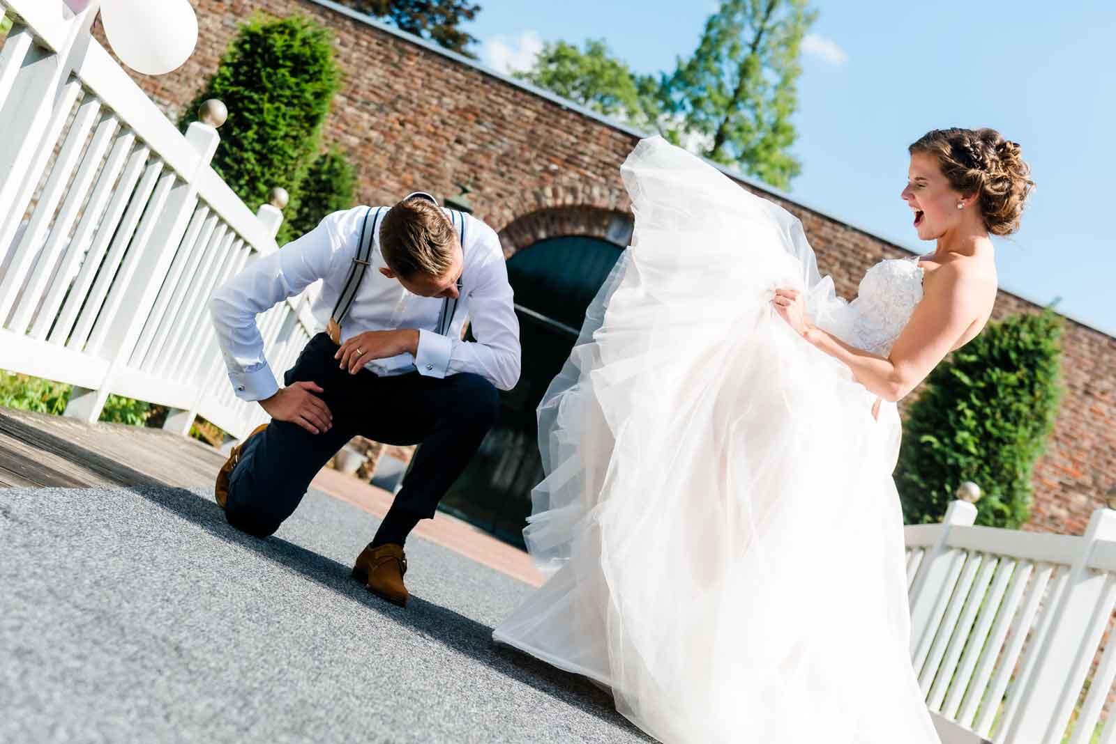 Bruid kijkt bruidegom onder de omhoog gezwiepte rok bij Kasteel Daelenbroeck herkenbosch
