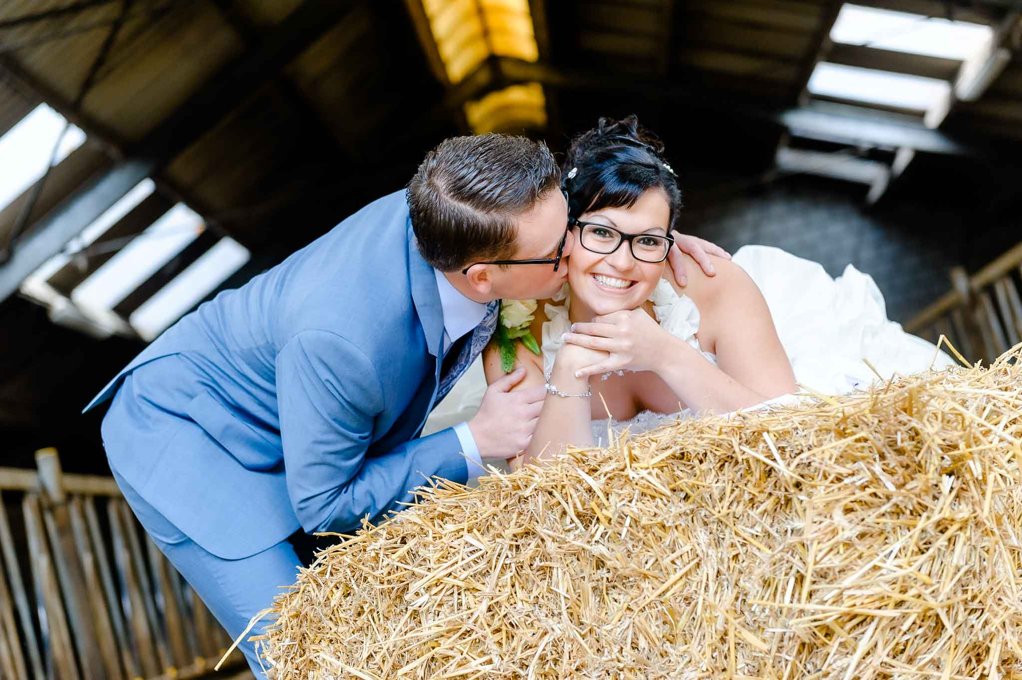Bruid ligt op het stro en bruidegom geeft een kus