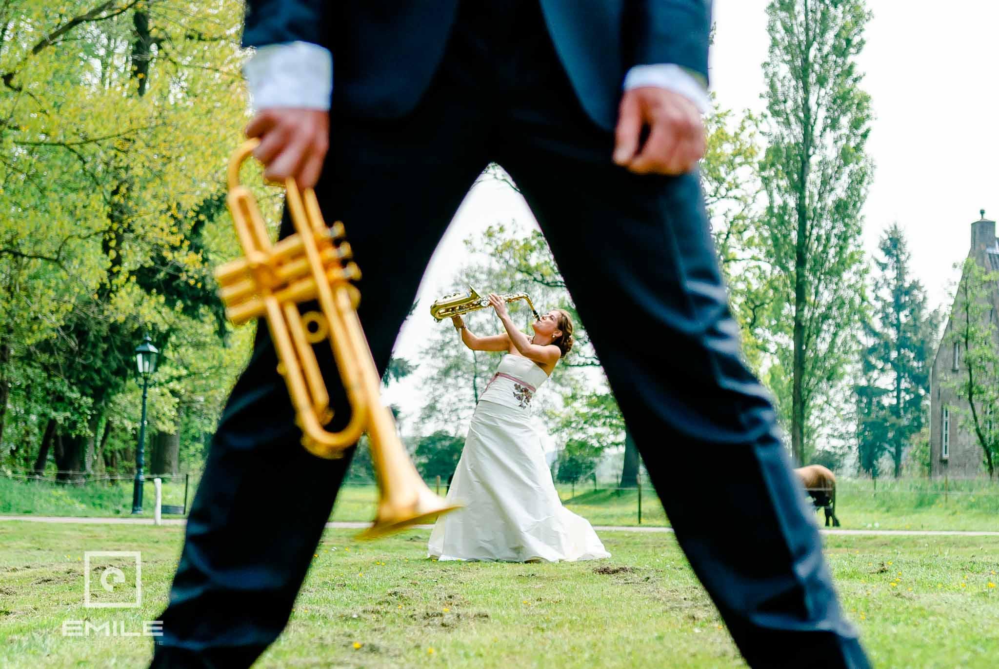 Bruid met saxofoon en bruidegom met trompet. Met de muziekinstrumenten in de wei van Kasteel Daelenbroeck Herkenbosch