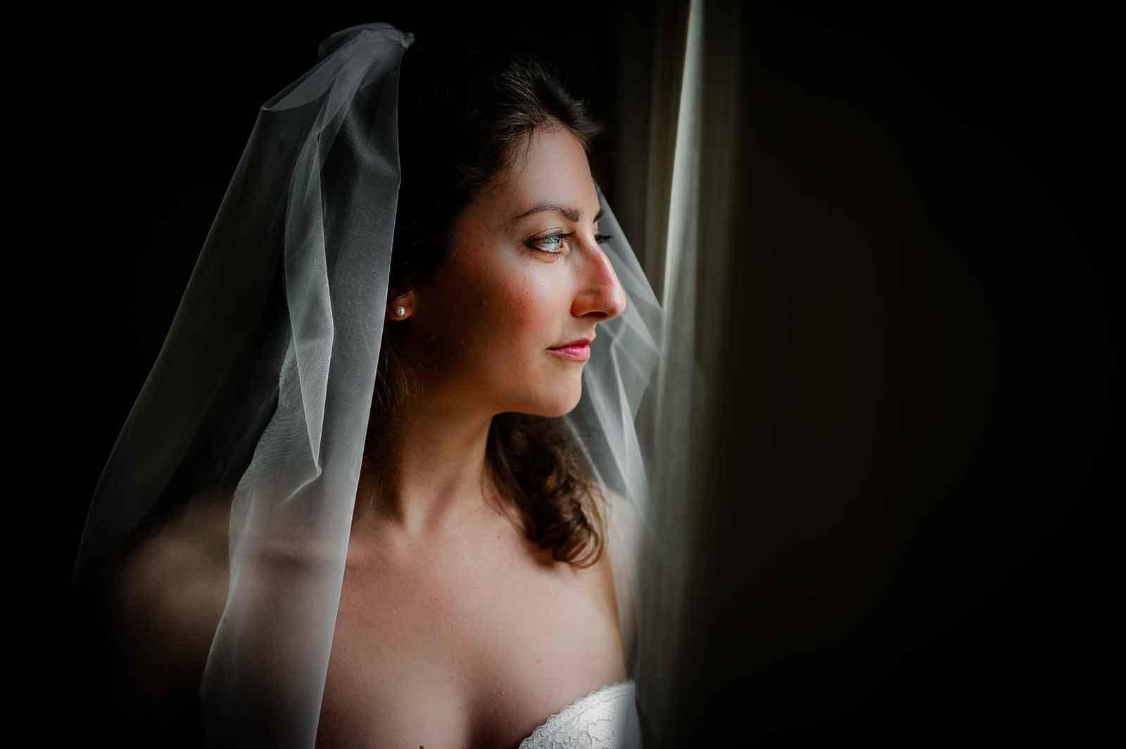 Bruid staat met de sluier bij de raam
