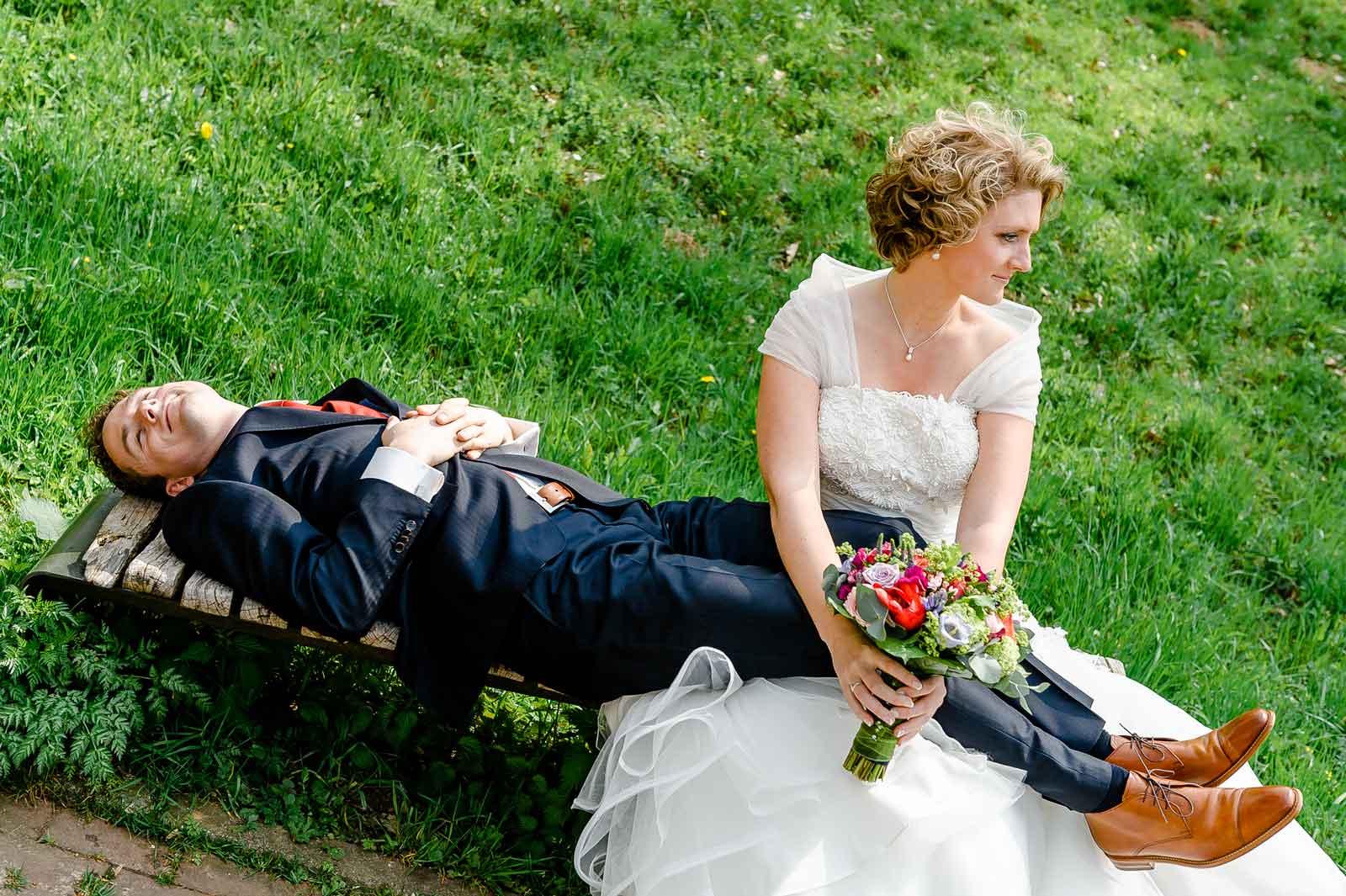 Bruidegom ligt te slapen op de schoot van de bruid. Samen op de bank bij Kasteel Elsloo