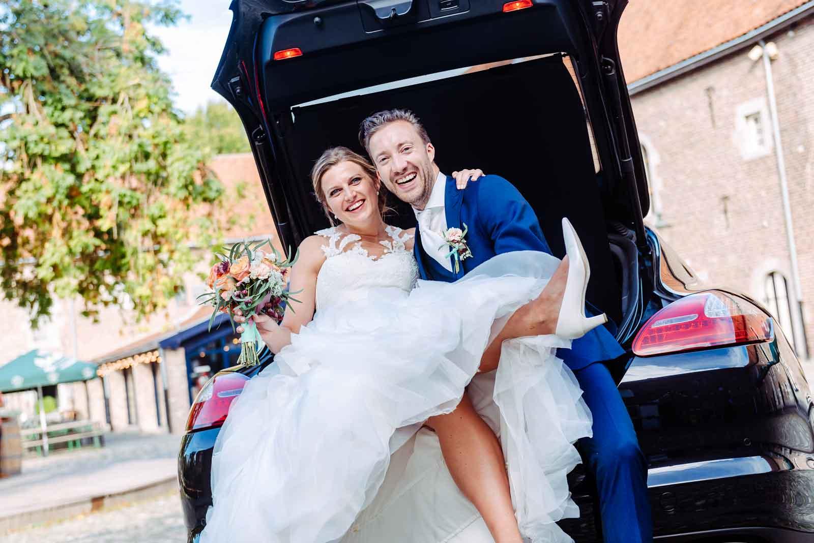 Bruidskoppel in de kofferbak van de Porsche trouwauto bij Kasteel Limbricht