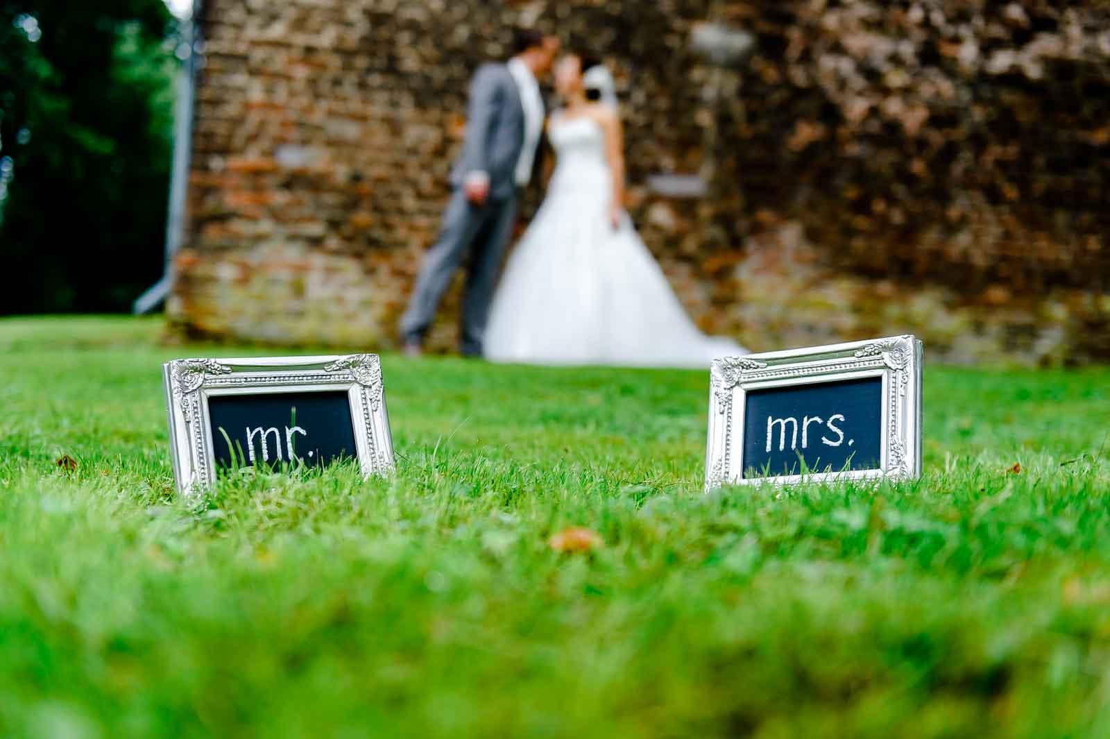 Bruidspaar met bordjes mister en misses in de tuin van Kasteel Horn bruidspaar onscherp op de achtergrond