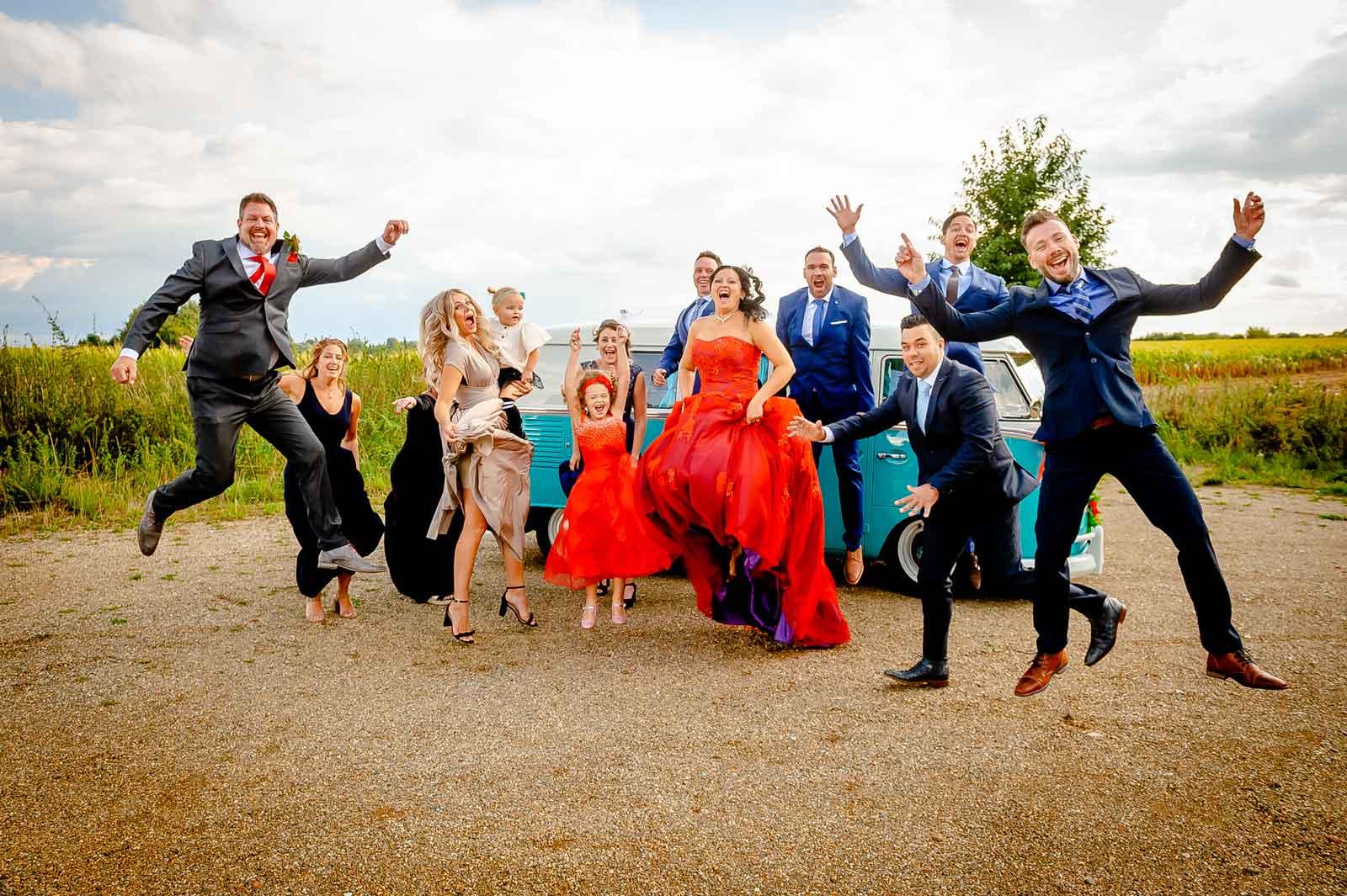 Bruidspaar springt samen met alle vrienden in de lucht