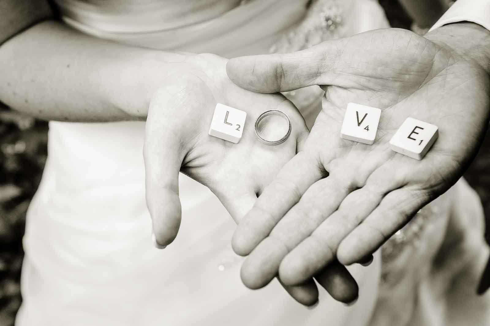 Handen van vers getrouwd koppel met de Scrabble letters love in de hand