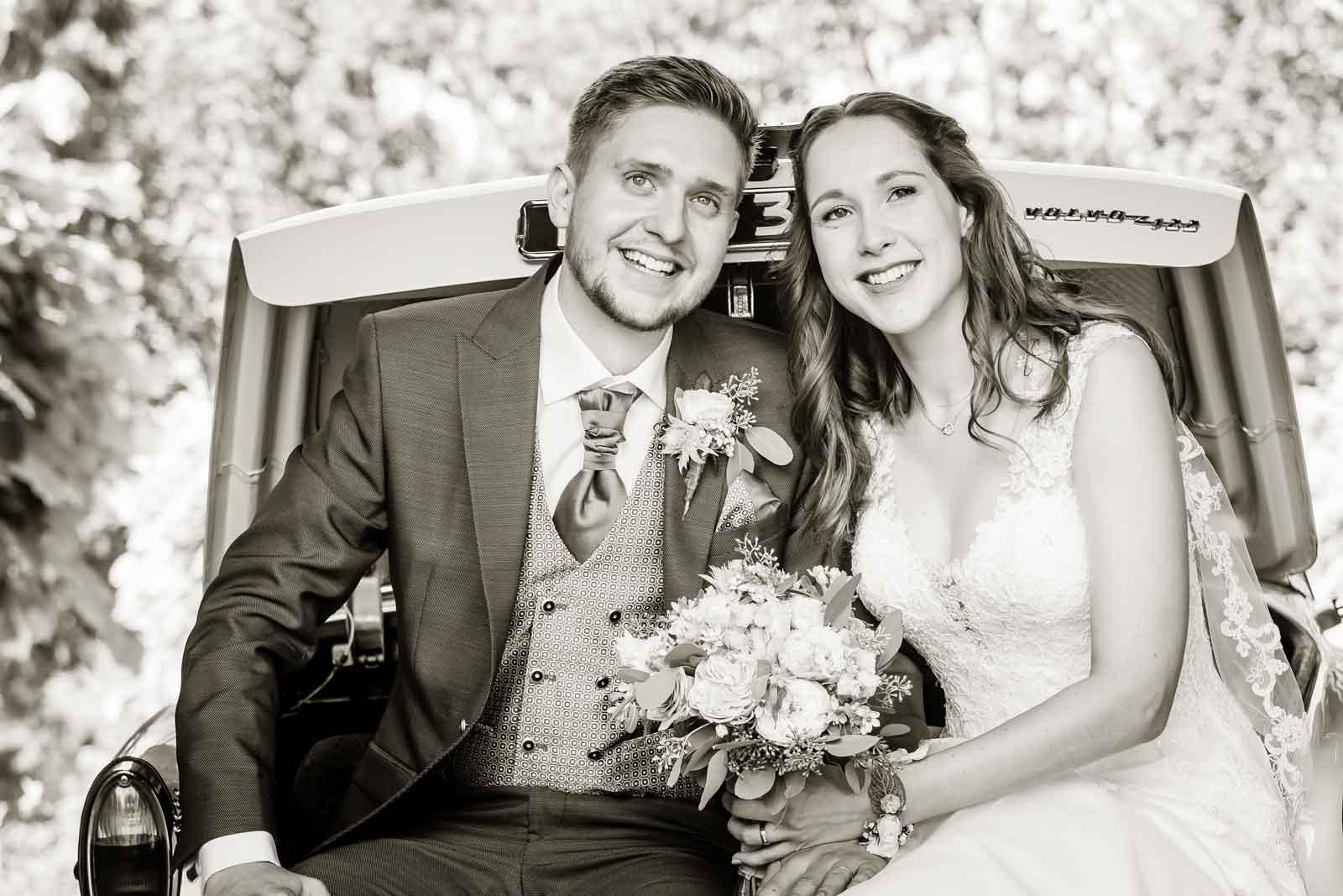 Kelly en Tom zitten vers getrouwd in de kofferbak van de auto bij Kasteel Erenstein te Kerkrade