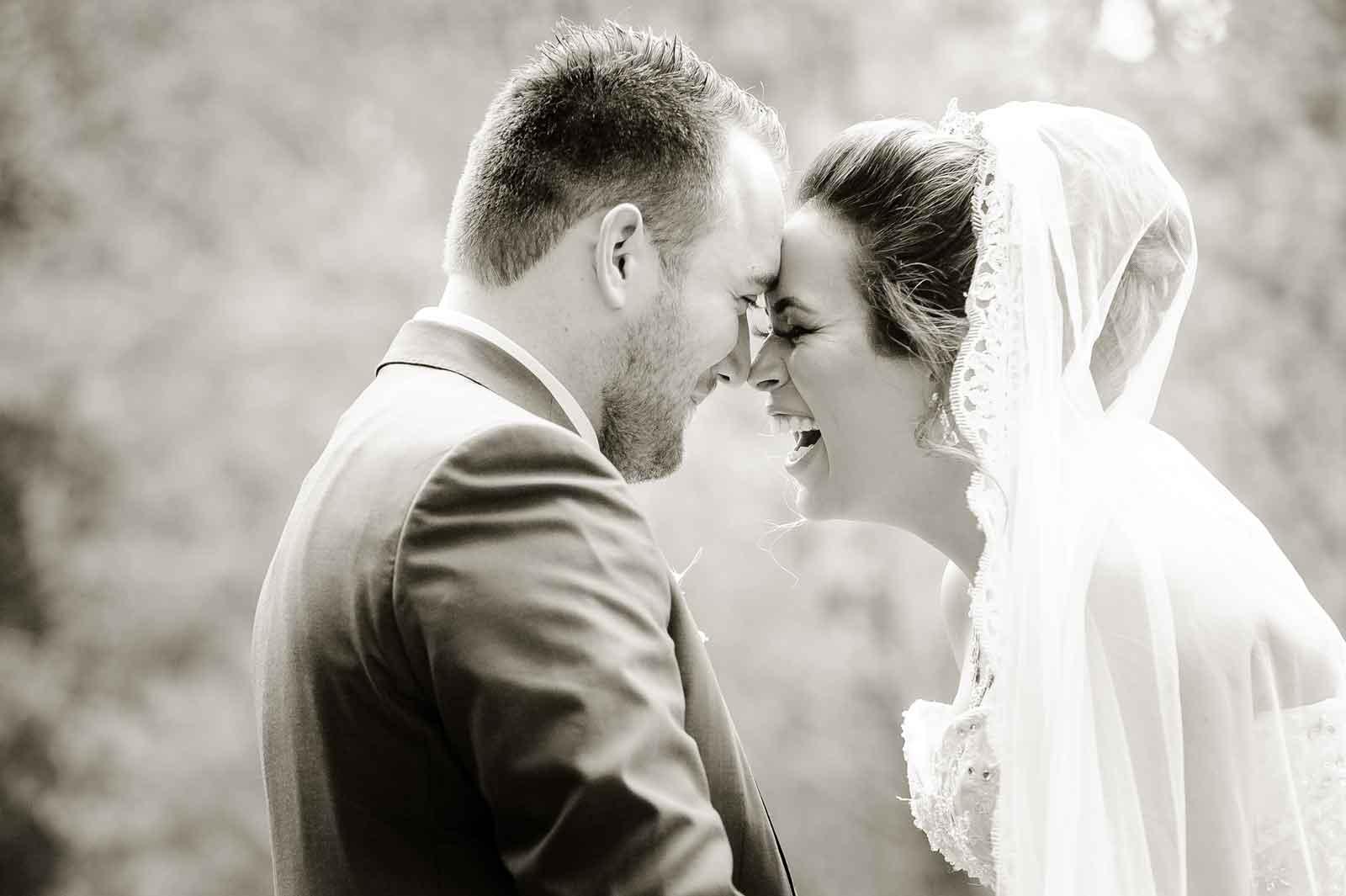 Lachend bruidskoppel bij Kasteel Elsoo aan het water - zwart wit