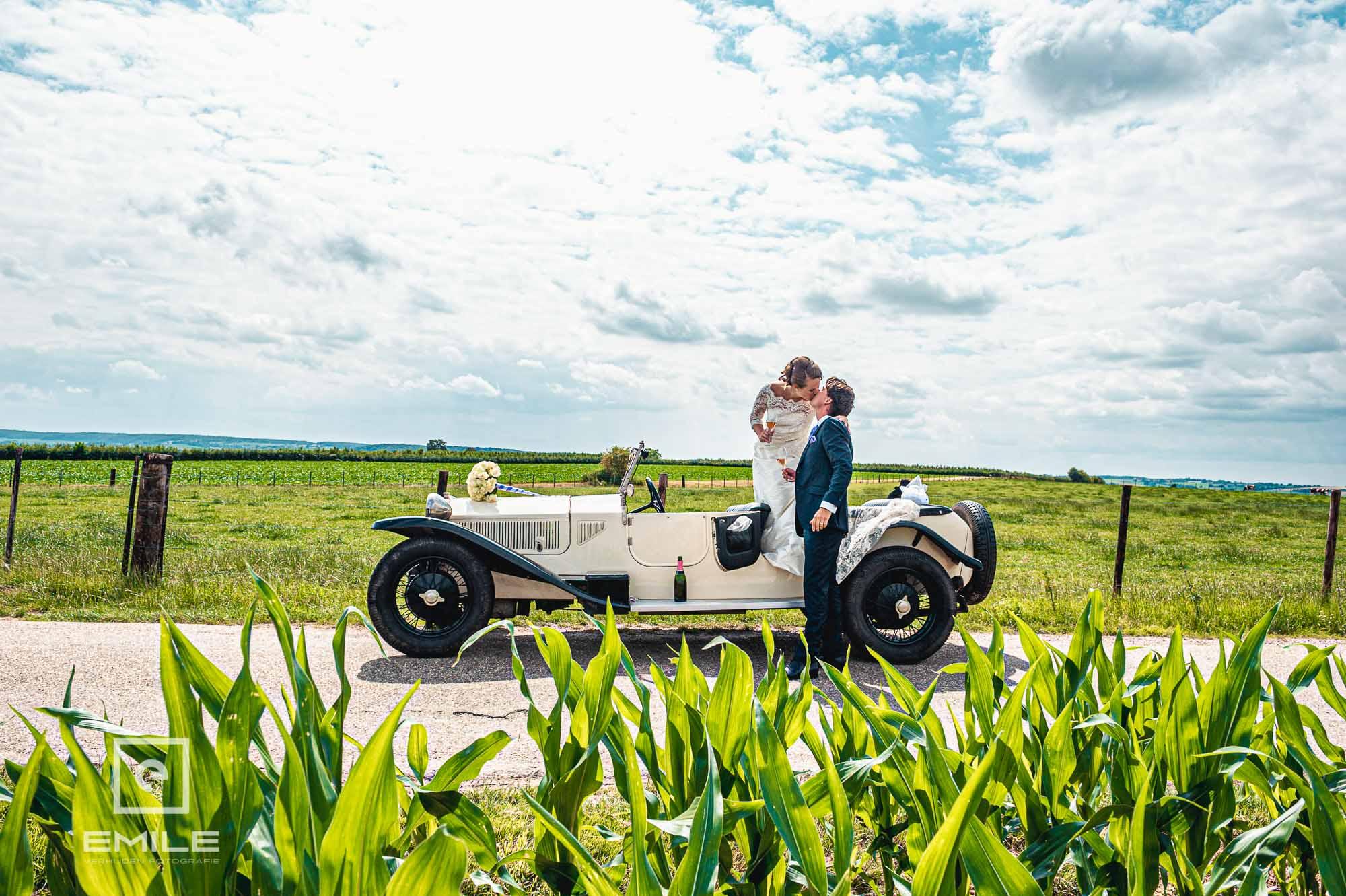 Bruid en bruidegom met old-timer in het prachtige Zuid-Limburgse landschap