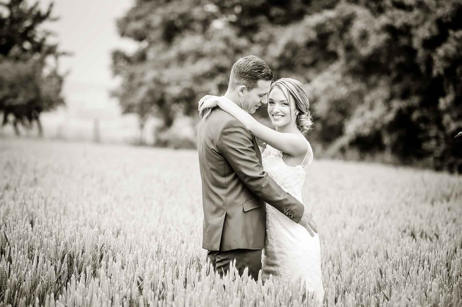 Net getrouwd en staan in het korenveld in Zuid-Limburg zwart-wit