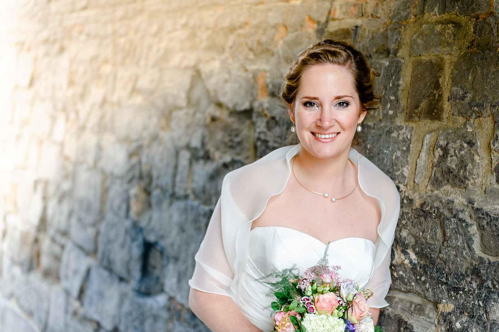 Stralende bruid bij helpoort Maastricht. Bruid heeft boeket in de handen