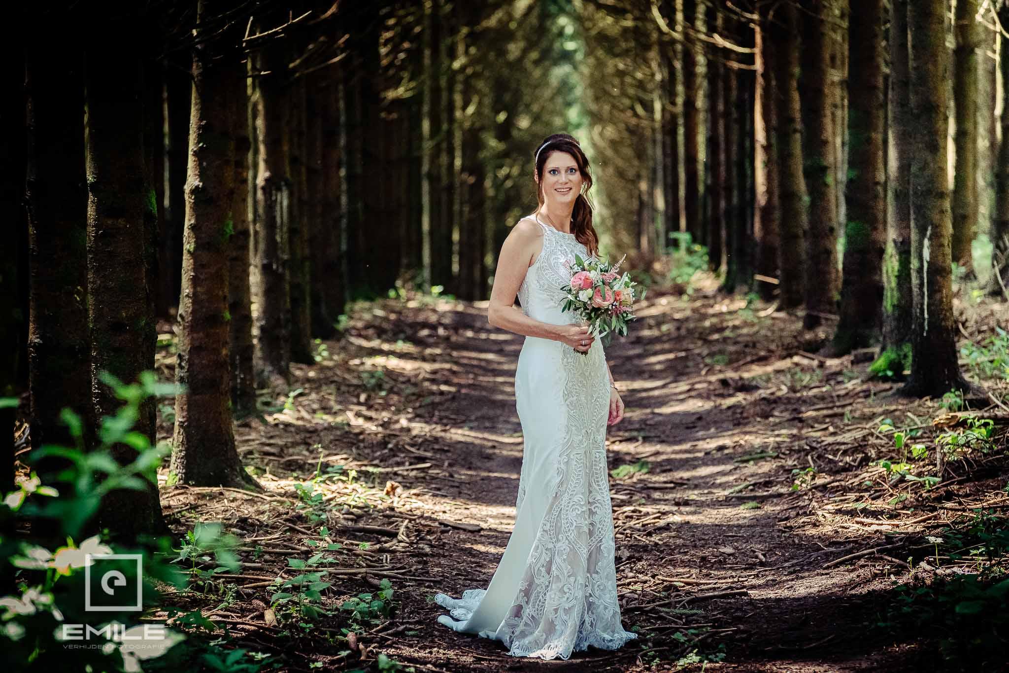In het bos van het Belgische Redu bruid vastgelegd tussen bomen