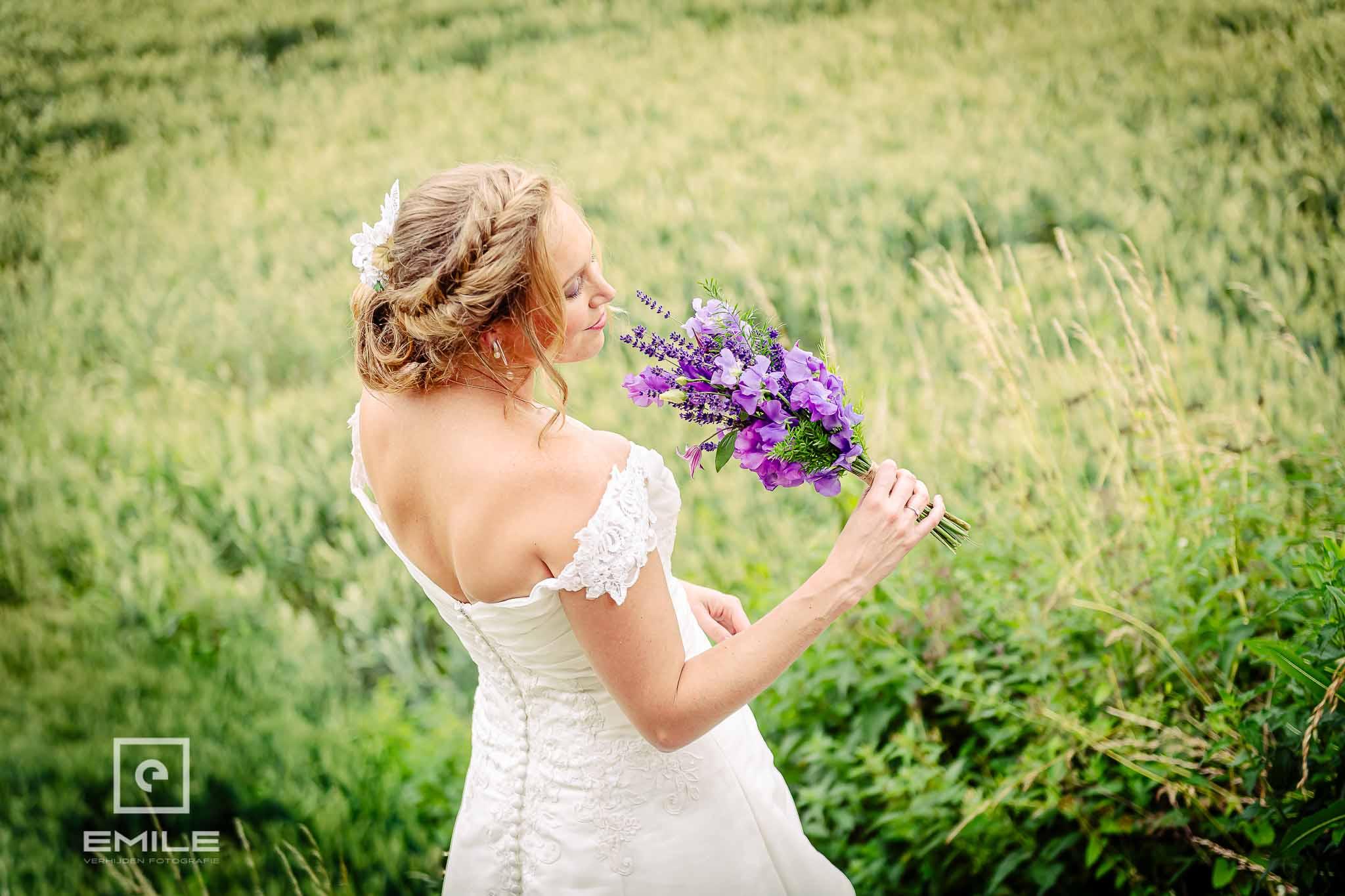 Prachtige bruid ruikt aan boeket staan in een korenveld