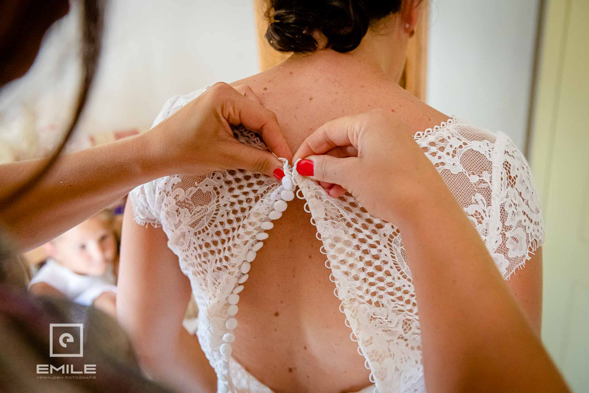 De bruidsjurk wordt dicht gemaakt - Destination wedding San Gimignano - Toscane Italie - Iris en Job