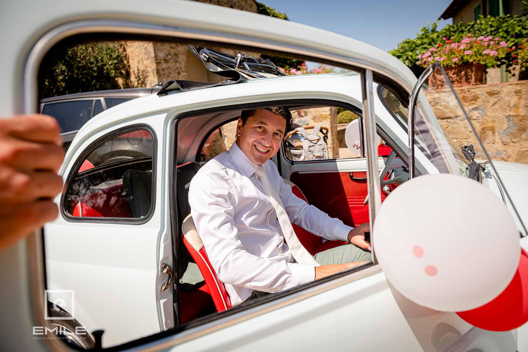 De bruidegom stapt in de FIAT 500 - Destination wedding San Gimignano - Toscane Italie - Iris en Job