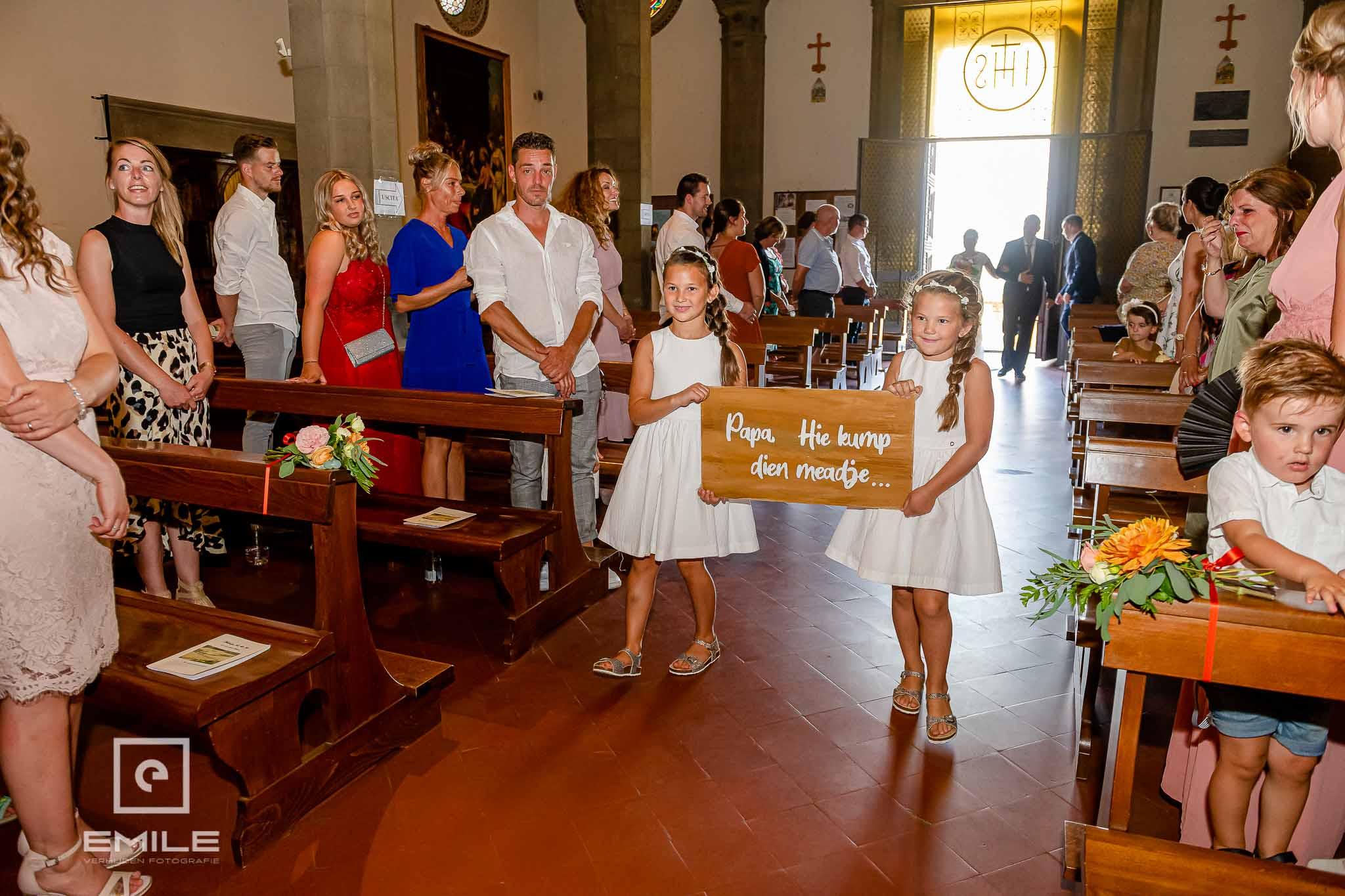 Kinderen met een bord met de Limburgse tekst Pappa hiej kumpt dien maedje - Destination wedding San Gimignano - Toscane Italie - Iris en Job
