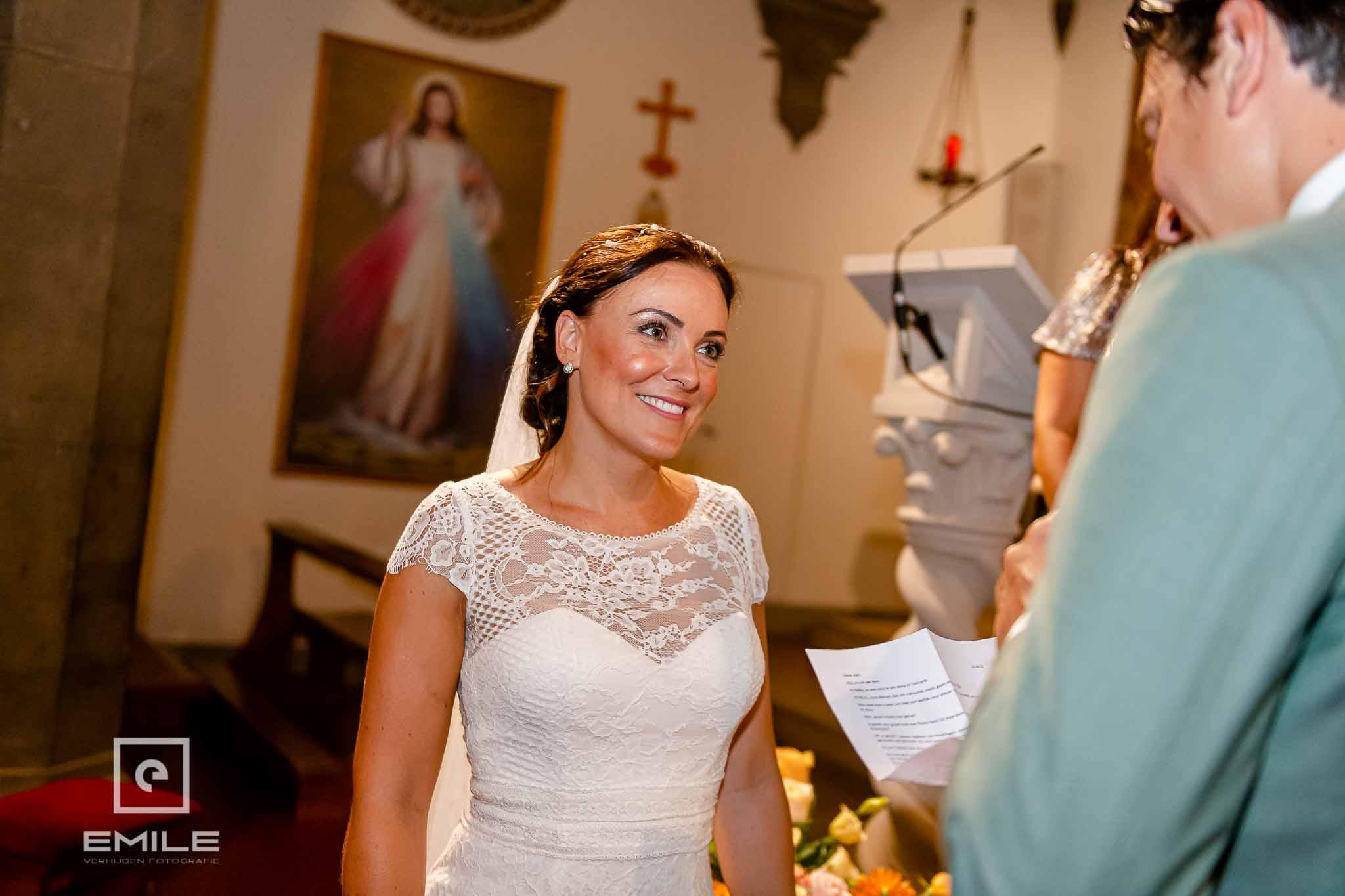 Stralende bruid luisterend naar de geloftes van de bruidegom - Destination wedding San Gimignano - Toscane Italie - Iris en Job