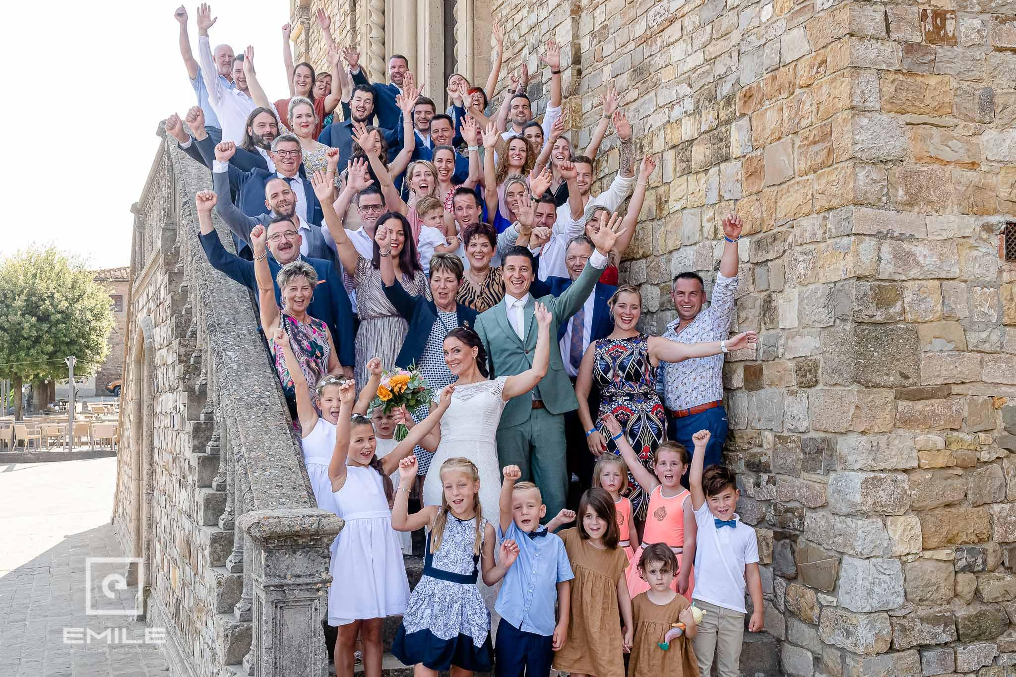 Groepsfoto voor de kerk - Destination wedding San Gimignano - Toscane Italie - Iris en Job