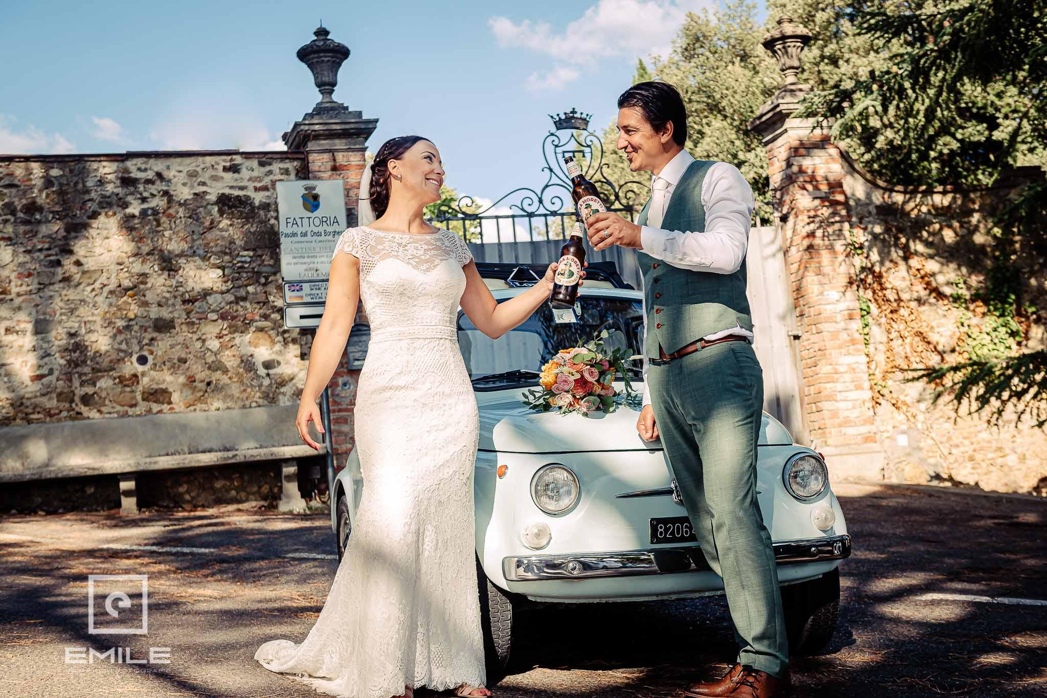 Bruidspaar even proostend met een Italiaans biertje - Destination wedding San Gimignano - Toscane Italie - Iris en Job