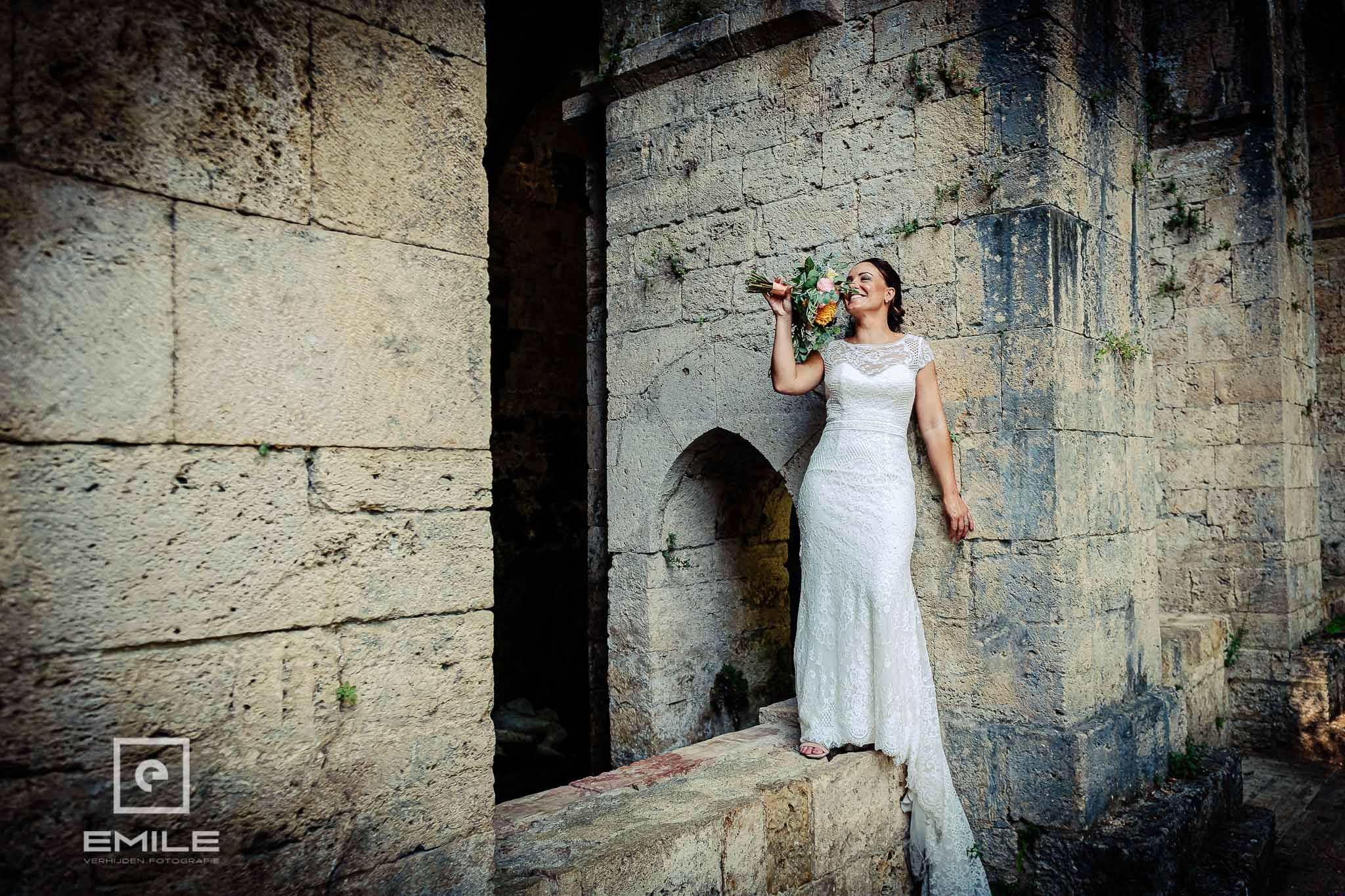 Bruid bij de ruine van Poggibonsi ruikend aan haar boeket - Destination wedding San Gimignano - Toscane Italie - Iris en Job