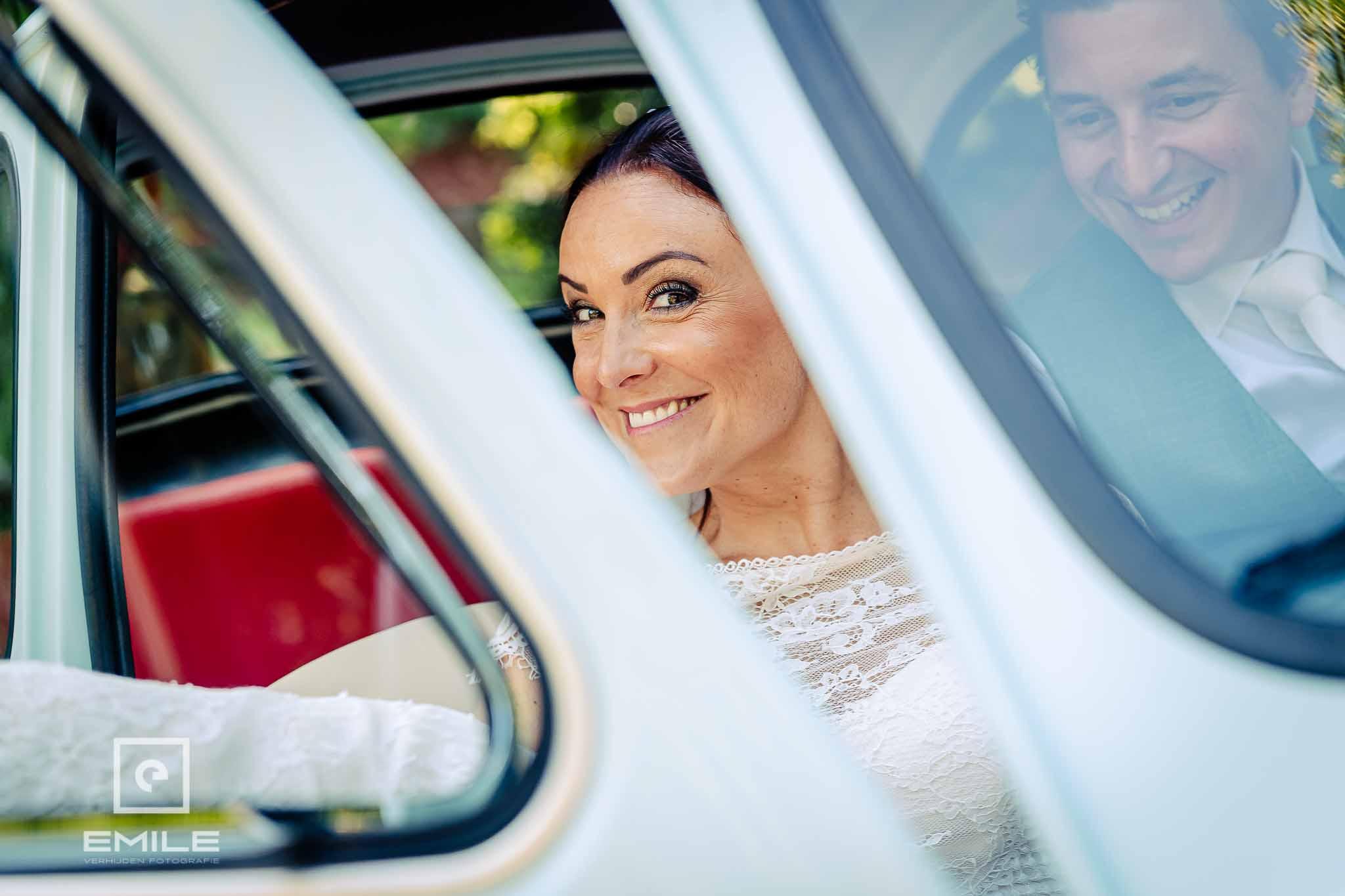 Happy bruid in de auto - Destination wedding San Gimignano - Toscane Italie - Iris en Job