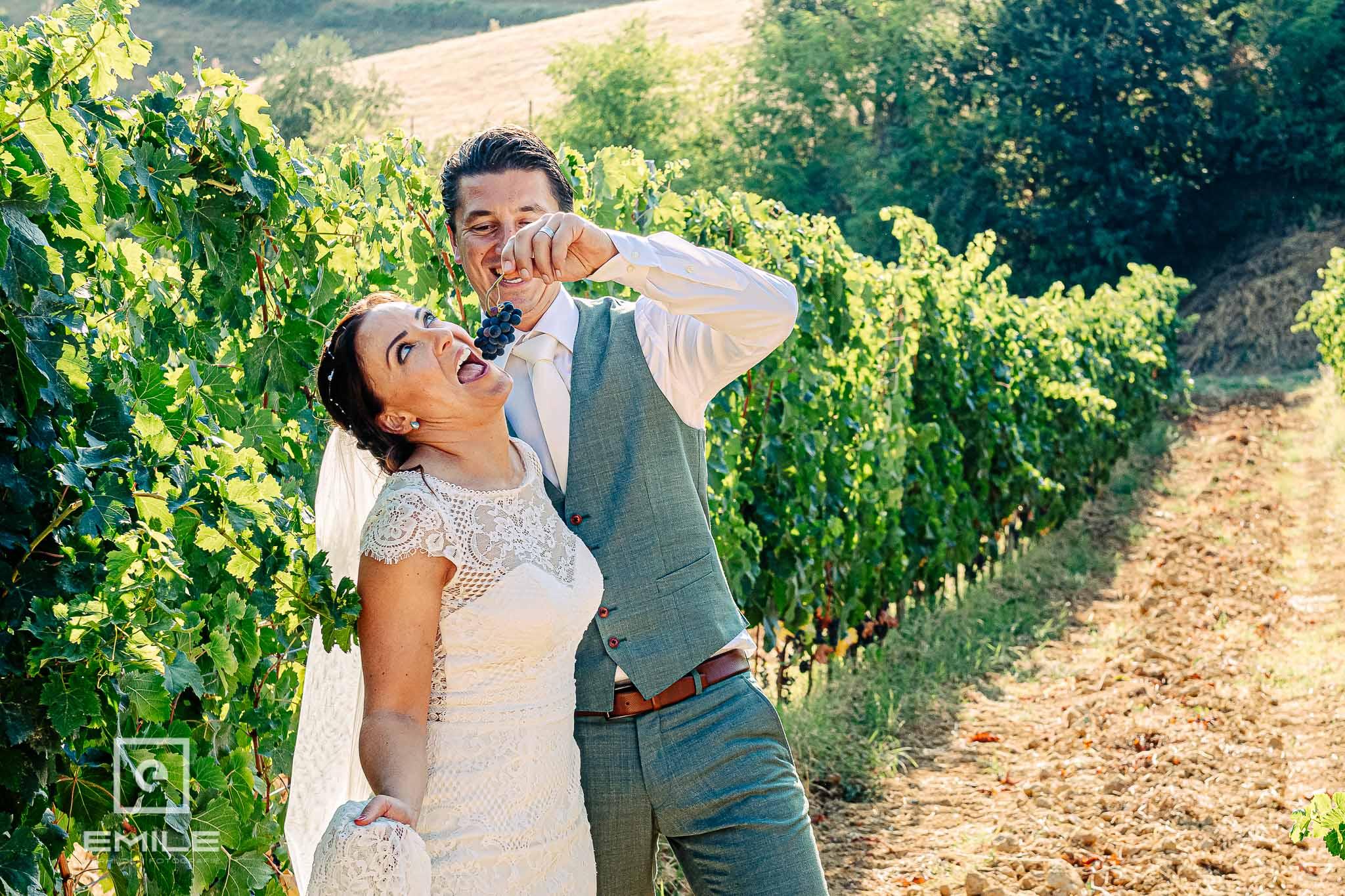 Bruid eet druiven in de wijnvelden- Destination wedding San Gimignano - Toscane Italie - Iris en Job