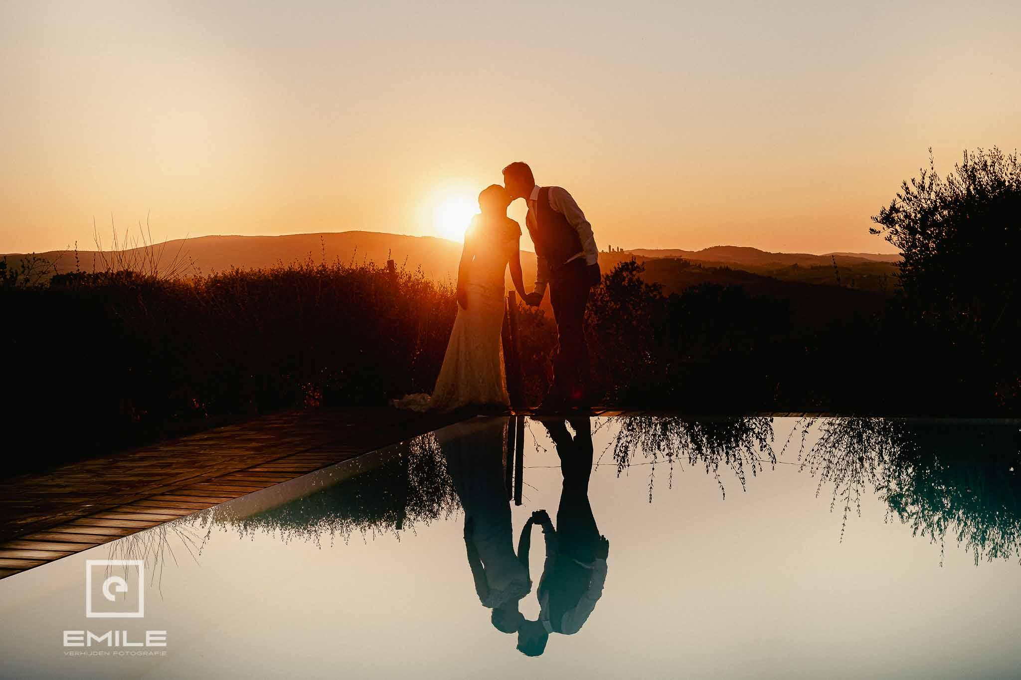Bruidspaar bij ondergaande zon staand bij het zwembad - Destination wedding San Gimignano - Toscane Italie - Iris en Job